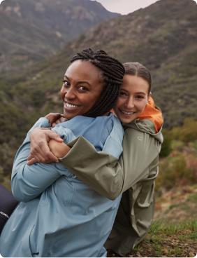 Two women hugging on a mountainside