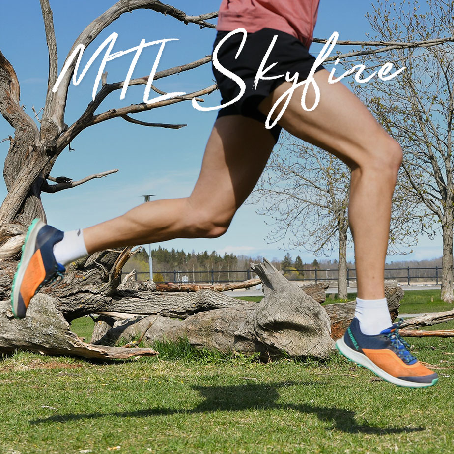Man running up a rocky mountainside wearing orange Skyfire shoes.