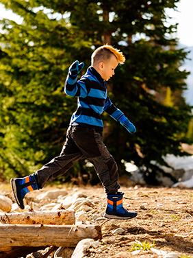 Kid runs in winter boots.