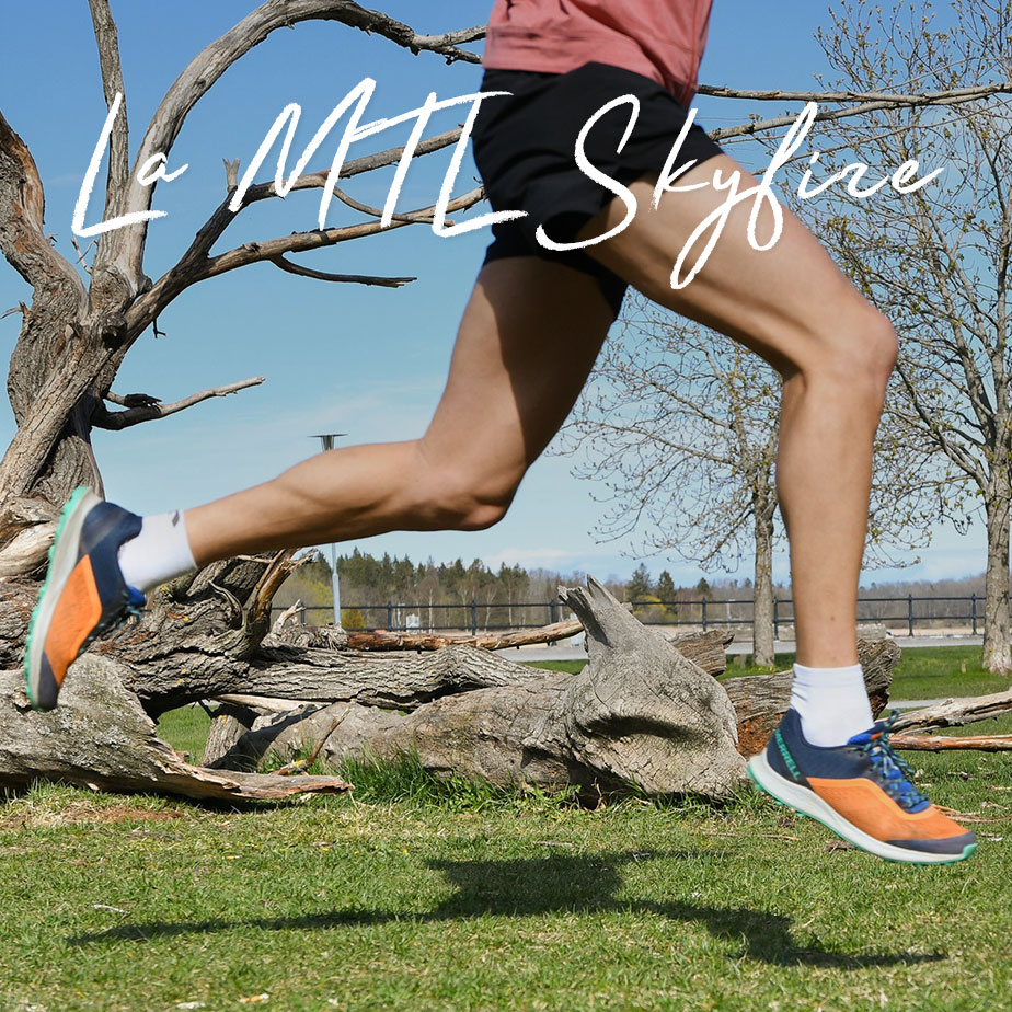Man running up a rocky mountainside wearing orange Skyfire shoes.