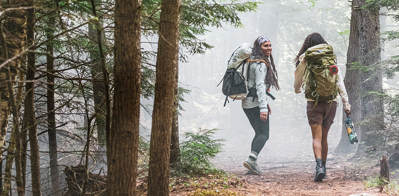 Two women are hiking in the wood.