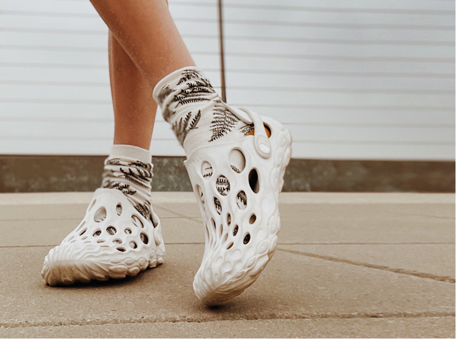 A Merrell Hydro Moc shoe on someone's legs.