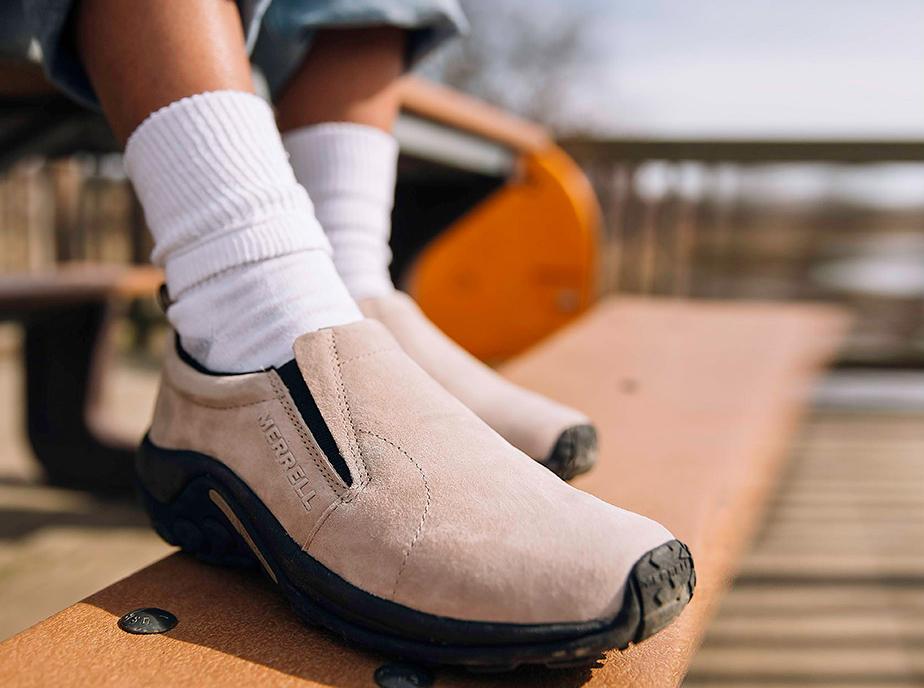 A Merrell Jungle Moc shoe on someone's legs.