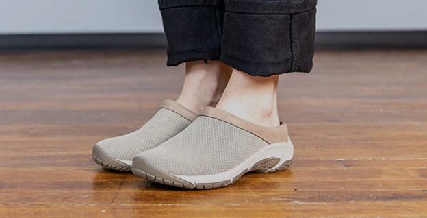 A close up of slip on shoes on a person.