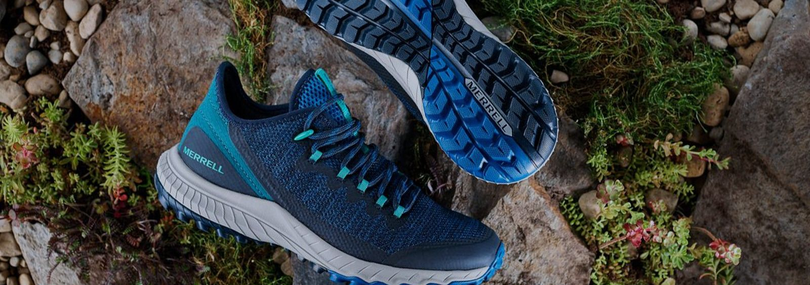 A pair of Merrell Bravada shoes on the rocks by some wildflowers