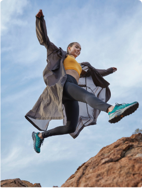 Woman jumping across rocks wearing Merrell hiking boots