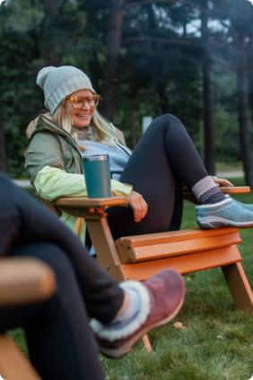 Woman relaxing in an adirondak chair with Merrell clogs