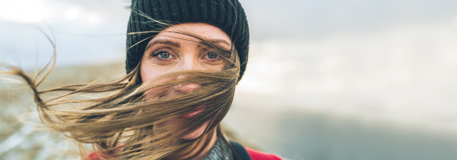 Rannvá Joensen with her hair blown in front of her face with the Faroe Islands in the background.