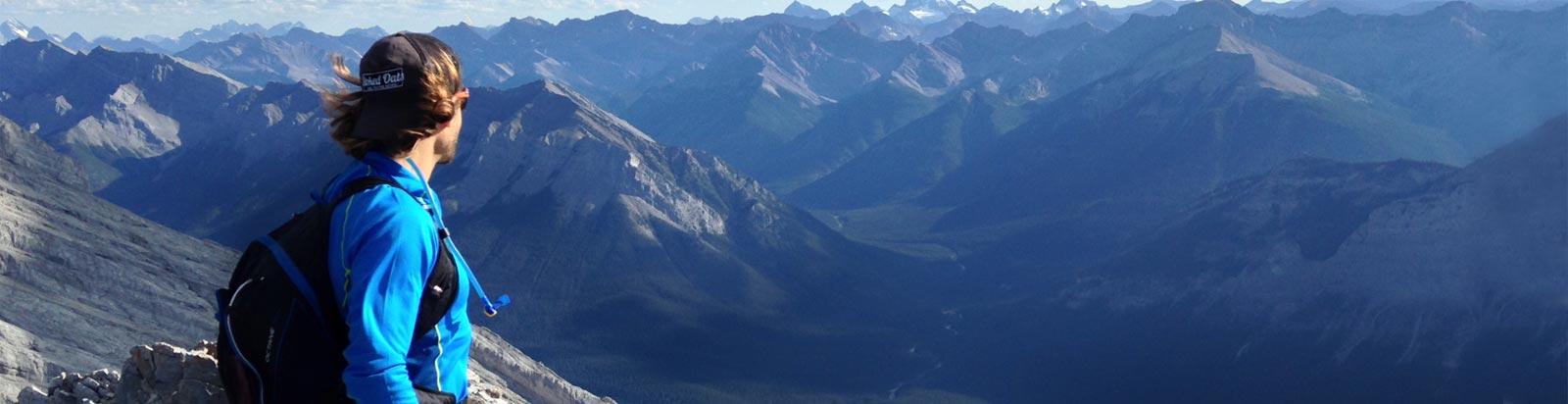 Merrell ambassador, looking off into a vast mountain vista.
