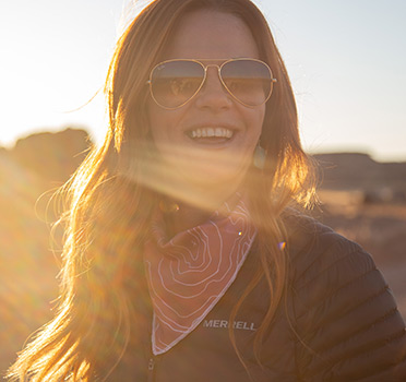 Nicole Brown is smiling while the dessert sun sets behind her.