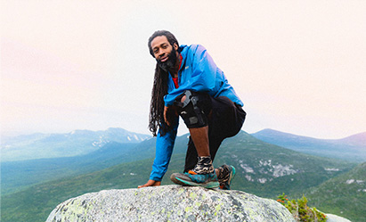 Will Robinson is crouching on top of a boulder on a mountain top.