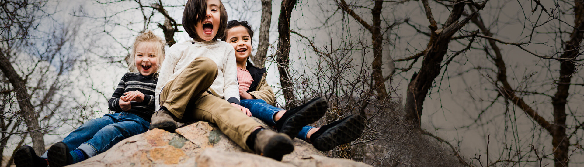 Three happy kids sat atop a large boulder among trees.