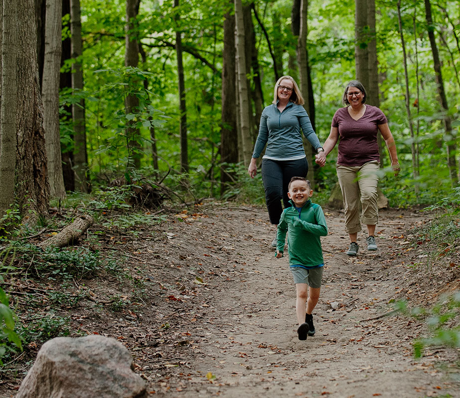 Two women holding hands, hikeing with a kid.