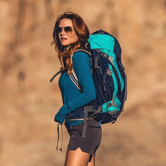 A brown-haired white woman in sunglasses stands on a trail, wearing a bright teal day pack with a dark blue shirt and athletic shorts.