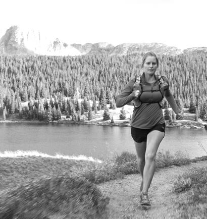 A runner rounds a corner on a trail. Behind and below her is a lake, and behind that a thick forest and a mountain.
