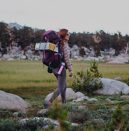 Woman hikes along a grassy trail.