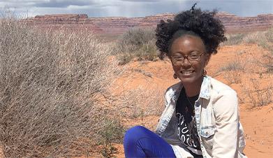 Latasha Dunston sitting in a desert setting.