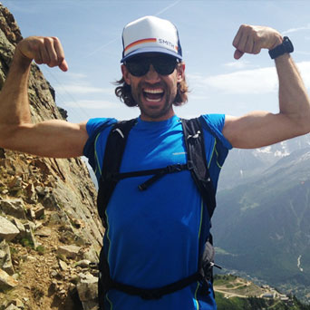 A dark-haired man in a baseball cap and a bright blue t-shirt grins and flexes both biceps in front of a mountain vista.