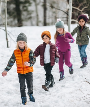 4 Kids walking single-file in the snow, wearing Merrell boots and apparel.