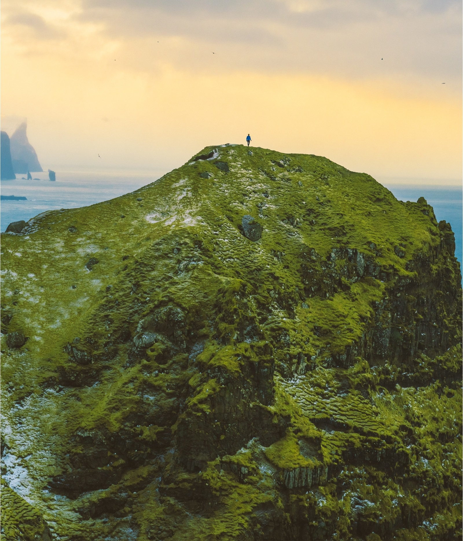 Person standing on top of a mountain.