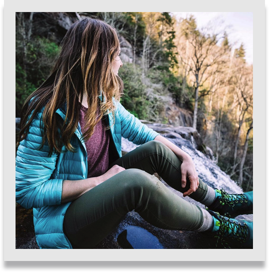 Female sitting on the mountainside, looking out over the natural splendor.