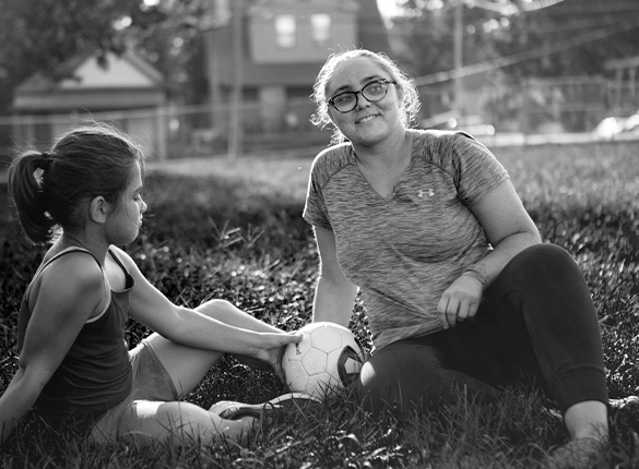 Child and adult sit on the grass, a soccer ball between them.