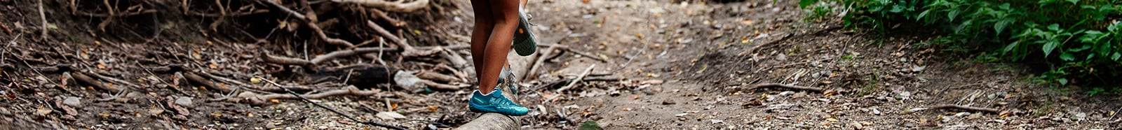 Two kids on a hike, balancing on a log wearing Merrell hiking shoes.