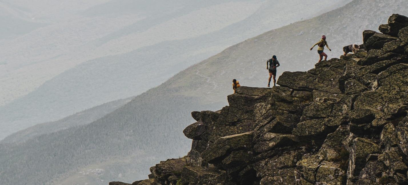 3 friends scrambling on a rocky mountain