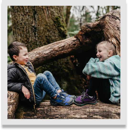 Two kids talking and laughing, sitting at the base of a tree in the woods.