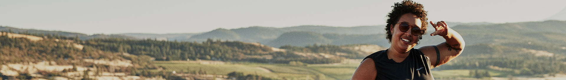 Smiling woman flashing a sideways peace sign with rolling hills and forests behind her.