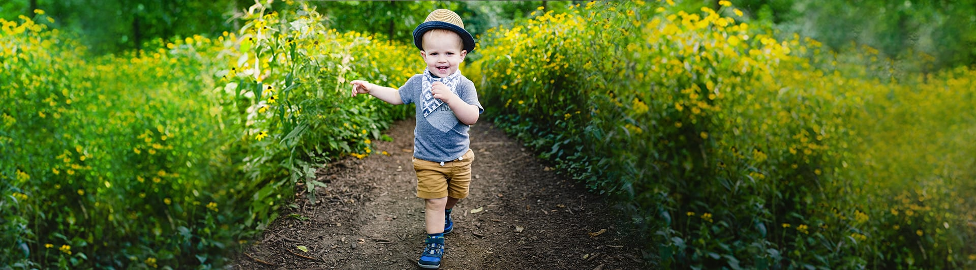 A smiling toddler hiking down a trail.