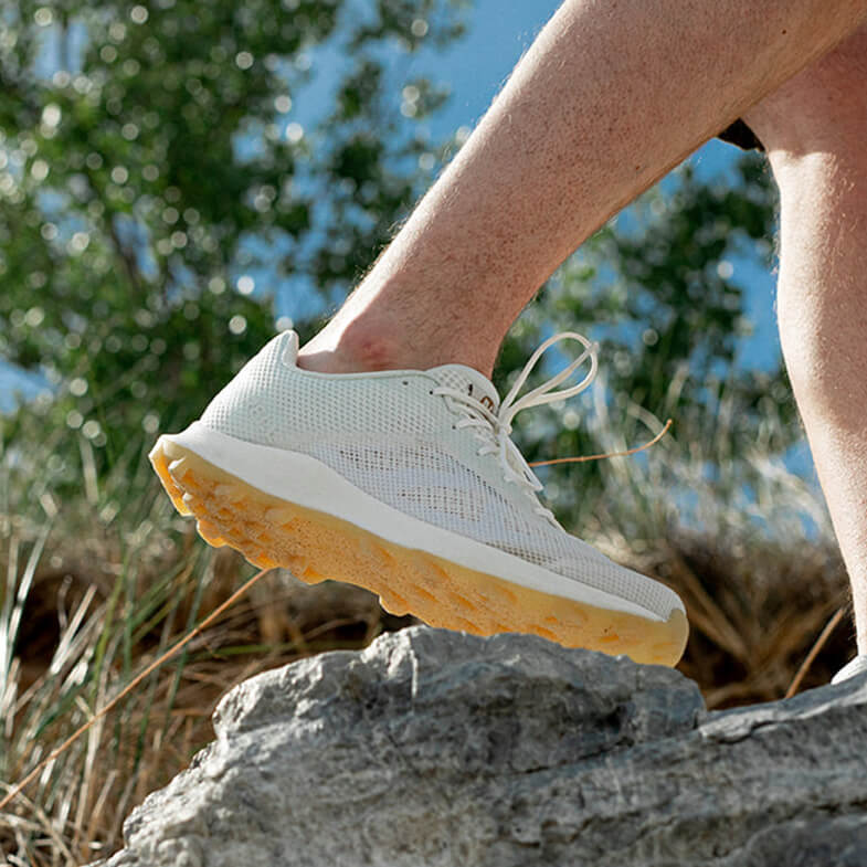 A foot wearing a an undyed shoe walks on a large rock.