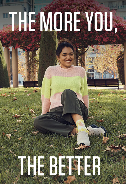 Laughing and sitting on grass in fall. Caption reads: The more you, the better.