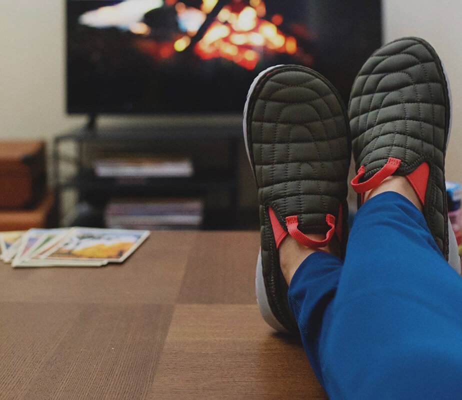 Feet wearing Cozy Hut Mocs up on a coffee table in front of a fire.