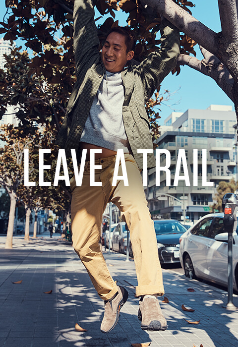 Swinging happily from a tree branch on a city sidewalk. Caption reads: Leave a trail.