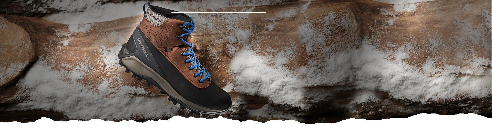 Merrell Kiruna Midshell boot in front of snowy rocks.