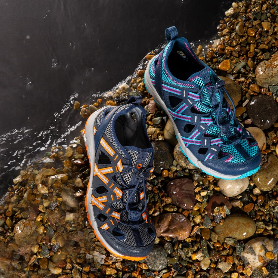 2 Merrell Kids Choprock shoes by a creek