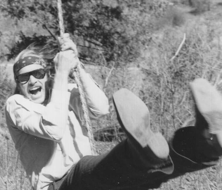 Clark Mattis is swinging on a rope, wearing a bandana, sunglasses and a big grin.