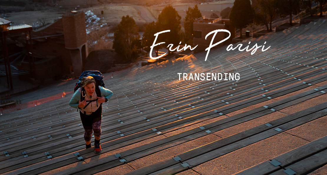 Erin Parisi climbing broad steps at dawn while wearing a large backpack.