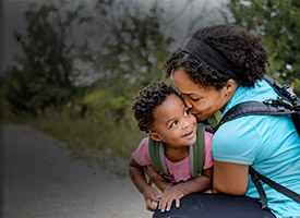 Mother wearing backpack is squatting down to hug her child.  Both are smiling and wearing Merrell hiking shoes.
