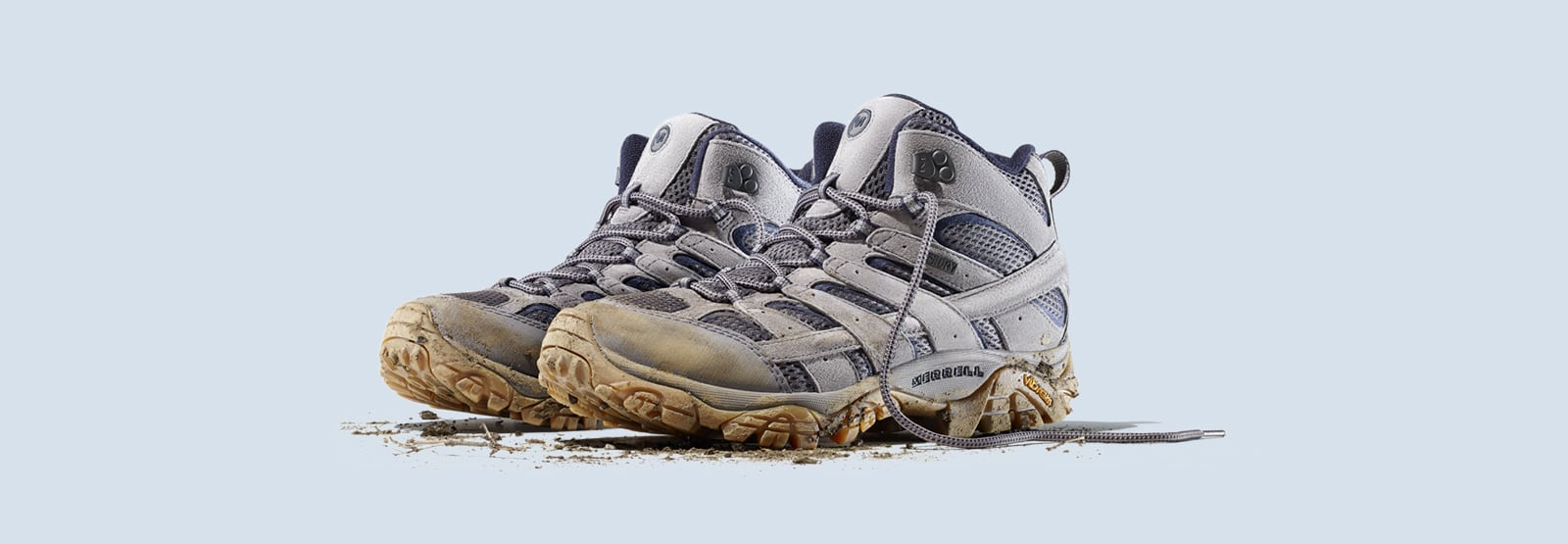 A pair of Grey and blue Merrell Moab boots, dirty and just off the hiking trail.