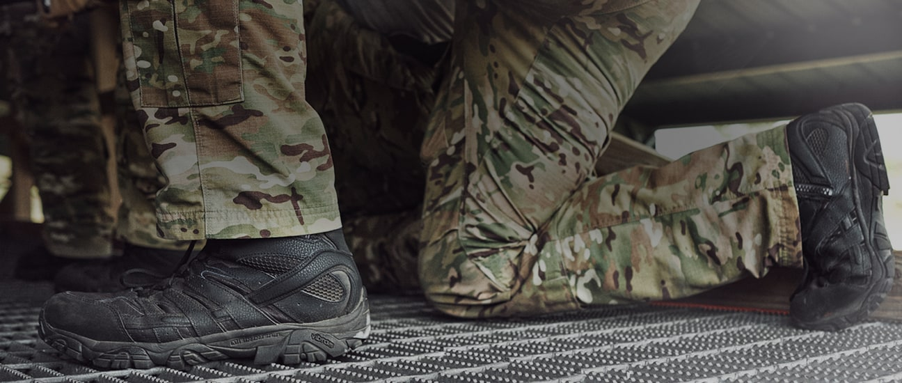 Person kneeling wearing camo pants and Merrell boots.