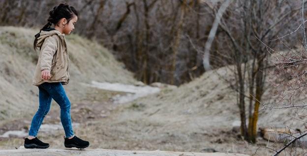 A kid hiking, wearing Merrell Jungle Mocs.