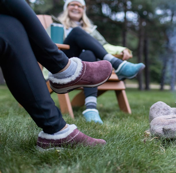 People sitting by an outdoor fire, wearing Merrell mocs.