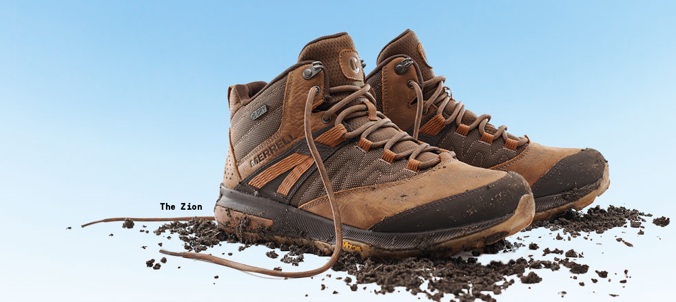 A pair of brown Zion hiking boots on top of dirt.