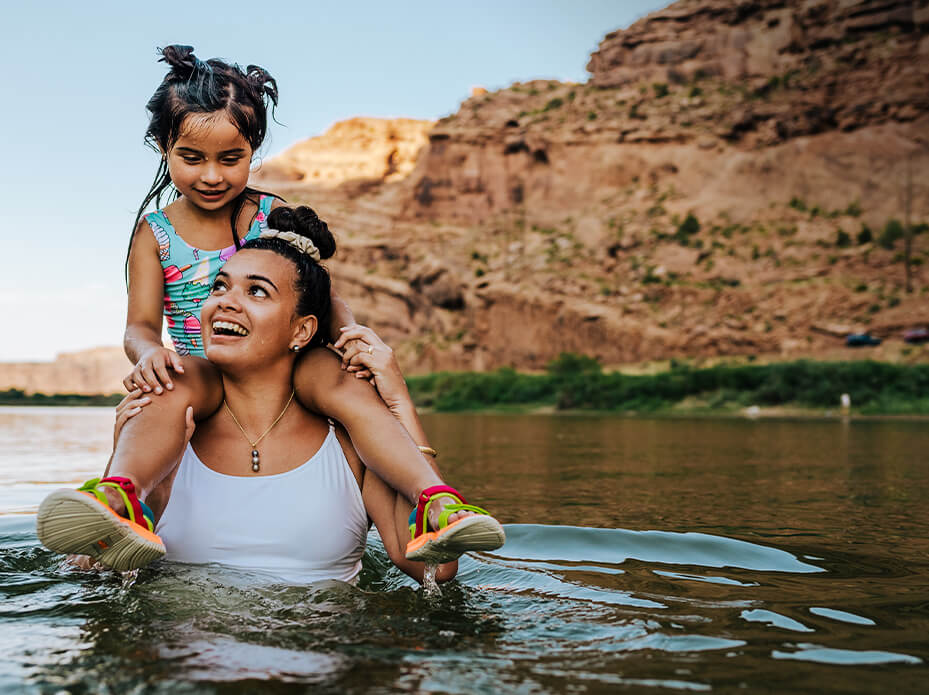 Adult with child on shoulders is chest deep in a lake.