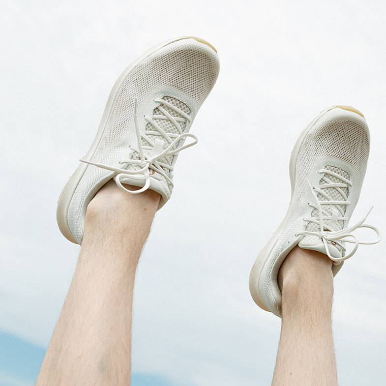 A pair of gently worn Undyed shoes on a pair of upturned feet against the sky.