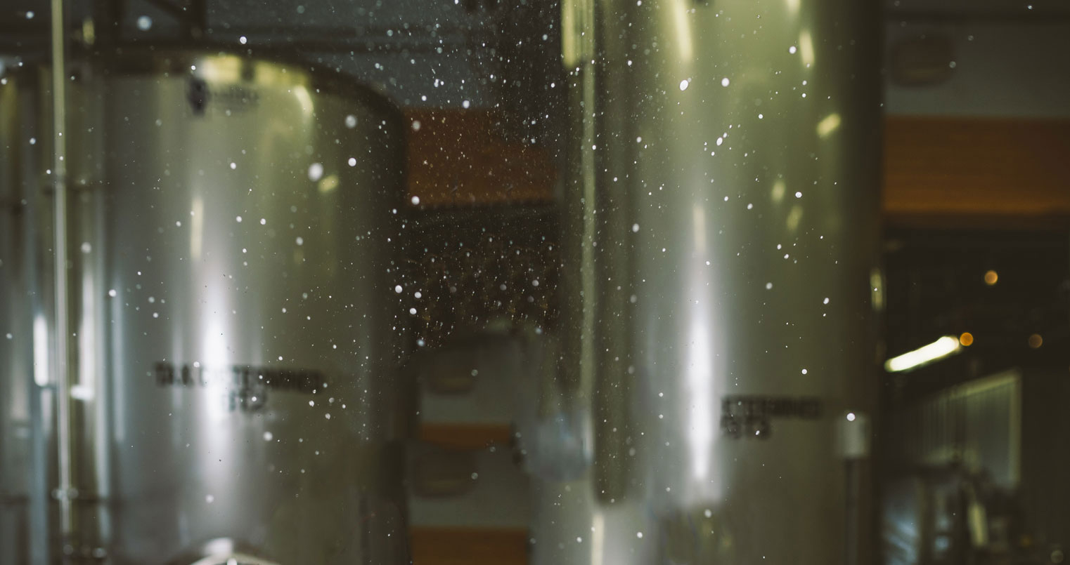 A man holds a foaming can of beer to his lips, droplets floating around his face.