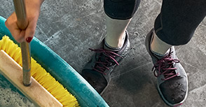 Close up of Merrell grey proe shoes with a person sweeping with a yellow broom.