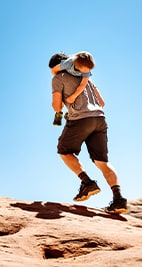 Man hiking with a kid on his back.